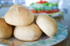 Home-made Dinner Rolls. A pile of whole-wheat dinner rolls on a plate with a salad in the background royalty free stock image