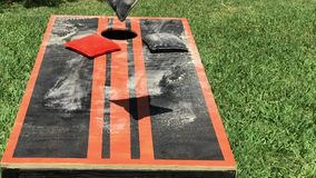 Home made dusty corn hole lawn game. Cornhole game with orange and black bean bags landing on target