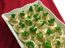 Home made devilled egg salad. With green parsley decoration. In a white porcelain tray on red tablecloth Stock Photos