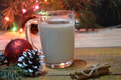 Home made Eggnog with cinnamon for Christmas and winter holidays. Against the backdrop of a Christmas tree with burning stock images
