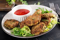Home made Fish Cake cod, spinach and breadcrumbs. Served on plate with sauce. Cutlets from minced cod. Delicious and nutritious lunch or dinner stock image
