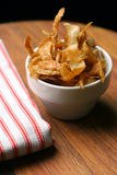 Home-made french fries and napkin. Crispy home-made french fries or potato chips served in a white ceramic bowl, striped napkin on wooden chopping block Stock Image