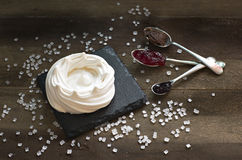 Home made fresh meringue on black stone. Teaspoons with jam and Royalty Free Stock Images