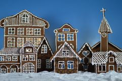 Home made gingerbread village with green background. Home made gingerbread village in front of green background on white snowlike velvet royalty free stock image