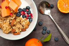 Home made Granola. Healthy home made breakfast of crunchy granola muesli, almonds, fresh melon, blueberries and pomegranate seeds. Served with fresh, sliced Royalty Free Stock Images