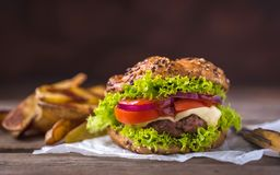 Home made hamburger with cheese and green salad and with american potatoes in behind. Wooden natural background.  stock image