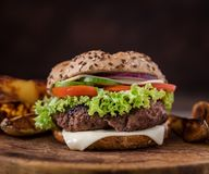 Home made hamburger with green salad and with american potatoes in behind. Wooden natural background. Home made hamburger with cheese and green salad and with stock photo