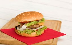 Home made hamburger on wooden table. Home made hamburger with onion, tomato, lettuce, cheese . close-up Royalty Free Stock Photos
