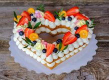 Home made heart shaped wedding cake. Beautiful homemade wedding cake in the shape of a heart , decorated with flowers and berries royalty free stock photography