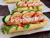 Home made hot dogs with vegetables, juicy sausage and arugula Royalty Free Stock Photos