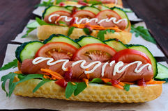 Home made hot dogs with vegetables, juicy sausage and arugula Stock Images