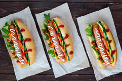 Home made hot dogs with vegetables, juicy sausage and arugula Stock Photography