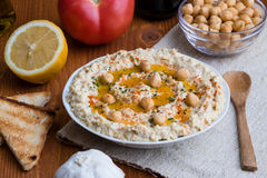 Home made hummus on wooden table Stock Photos