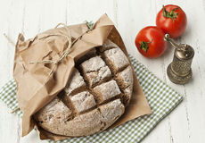Home made integral rye bread. Taken on green kitchen towl and wrapped in brown paper with fresh tomatoes and pepper mill Royalty Free Stock Photography
