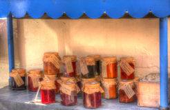 Home made jams and preserves for sale in pots with labels in colourful HDR. Home made jams and preserves for sale in pots with labels and honesty box for payment Stock Photo