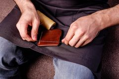 Home made leather brown wallet small business. Men's hands sewing stock image