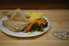 Food photography of a healthy homemade lunch with tuna fish sandwich on brown bread and side salad with love heart decoration. A home made lunch with canned tuna Royalty Free Stock Image