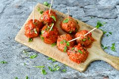 Meat balls with tomato sauce and fresh parsley on cutting board stock image