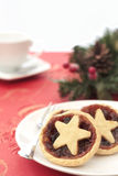 Home made mince pies. Star topped sweet mince pies on a plate. There is a festive red and gold tablecloth, and red and green berry decoration in the background Stock Image