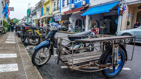 Home made motorcycle with sidespan. Motorcycle with makeshift sidecar in Phuket Old town, Thailand. Blue rims and shockbreakers on this moped. Colourful houses Royalty Free Stock Photography