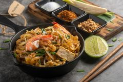 Home Made Pad thai with Shrimp and Vegetables on Marble table. Close up Thai Fried Noodles and Seasoning with Lemon There is a brown paper to tag the word stock photography