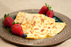 Home made pancakes. Fresh home made pancakes served on a rustic plate with strawberries and blueberries Stock Photos