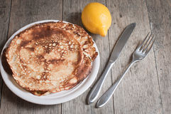 Home made pancakes with lemon and sugar topping seen against a textured wooden background Royalty Free Stock Photography