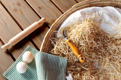 Home made pasta. Traditional basket filled with tagliatelle royalty free stock images
