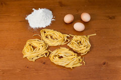 Home-made pasta and ingredients. With flour and eggs over a wooden table Royalty Free Stock Photos