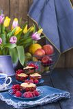 Home-made pastries with red currants and raspberries. Cupcakes for breakfast. A bouquet of spring flowers. Tulips yellow and red. Card Stock Photography