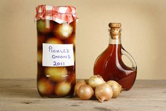 Home made pickled onions. Jar of home made pickled onions on a wooden table Royalty Free Stock Images