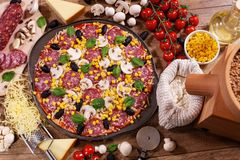 Home made pizza with ingredients on the table - top view Royalty Free Stock Image