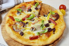 Home made pizza with smoked sausage, olives, tomates, cheese and basil on a olive wood cutting board. Royalty Free Stock Photo
