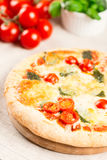 Home made pizza on wooden board with tomatoes on background Stock Photography