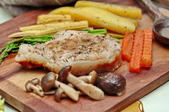 Home made ,Pork steak and mixed vegetables on butcher served. Selective focus. Royalty Free Stock Images