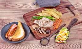 Home made ,Pork steak and mixed vegetables on butcher served served with side dish as parmesan cheese bread ,sausage ,shiitake fre Royalty Free Stock Photo