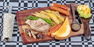 Home made ,Pork steak and mixed vegetables on butcher served served with side dish as parmesan cheese bread ,sausage ,shiitake fre Royalty Free Stock Photography