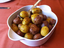 Home made potato dish. In a white porcelain bowl, ready to be served. Red tablecloth Stock Image