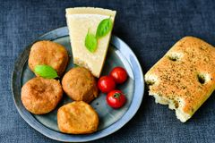 Home made   potatoes Croquette. Potato pancake or croquette , hand made ciabatta bread with olives and spices , parmesan cheese and cherry tomatoes Royalty Free Stock Photos