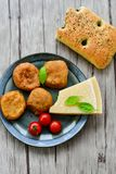 Home made   potatoes Croquette. Potato pancake or croquette , hand made ciabatta bread with olives and spices , parmesan cheese and cherry tomatoes Stock Photos