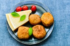 Home made   potatoes Croquette. Potato pancake or croquette , hand made ciabatta bread with olives and spices , parmesan cheese and cherry tomatoes Royalty Free Stock Photo