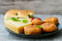 Home made   potatoes Croquette. Potato pancake or croquette , hand made ciabatta bread with olives and spices , parmesan cheese and cherry tomatoes Royalty Free Stock Images