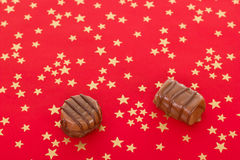 Home-made pralines on red background. Two delicious home-made pralines on red background Stock Photo