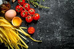Home made raw pasta with thyme, eggs, oil and tomatoes. On black rustic background royalty free stock images