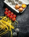 Home made raw pasta with tomatoes on a branch, eggs and spices. On black rustic background royalty free stock images