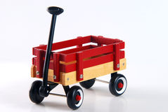Home made Red Wagon. Home Made Wagon with a plain wood bottom, and two red wood planks on top. Black handle and wheels with white walls Stock Photo