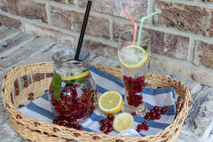 Home-made refreshing lemonade of red currant with ice and lemon royalty free stock image