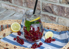 Home-made refreshing lemonade of red currant with ice and lemon royalty free stock photography