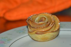 Home-made rose-shape apple pie on a plate. Home-made rose shape apple pie on a white plate. The pie is fresh, just out off oven. The plate is white with pin Stock Photo