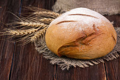 Home-made round bread and wheat on the wooden table royalty free stock image